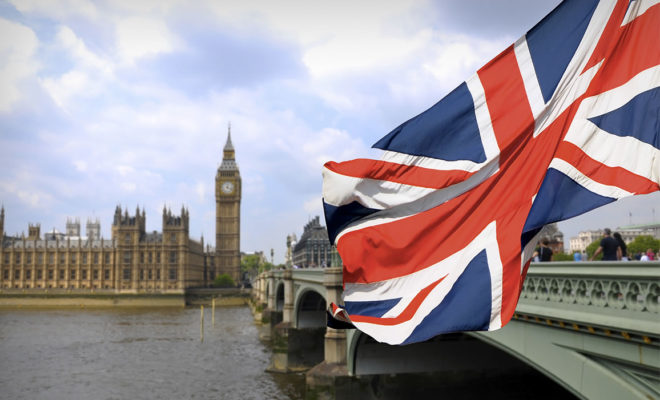 PHOTO: British flag flying in foreground, Thames River and Parliament in background.