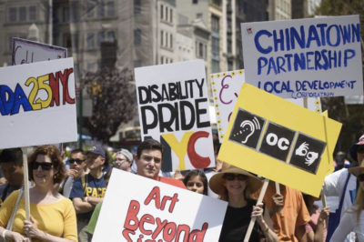 PHOTO: A group of people with disabilities holding signs and participating in a disability pride march.
