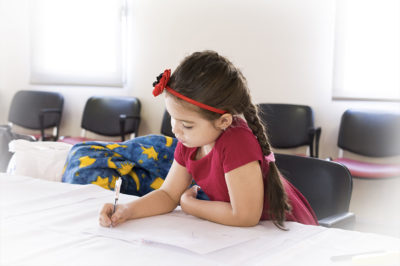 PHOTO: Young girl with pen in hand working on a project at her school classroom desk.