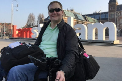 """PHOTO: Wheelchair traveler John Morris takes a selfie in front of the """"I Amsterdam"""" sign."""