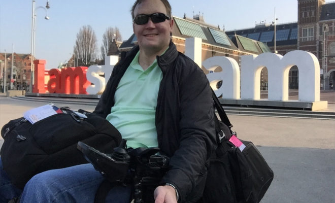 "PHOTO: Wheelchair traveler John Morris takes a selfie in front of the ""I Amsterdam"" sign."